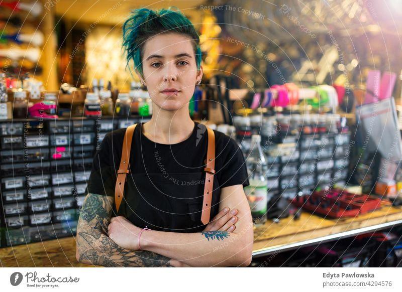 Selbstbewusste junge Frau bei der Arbeit in der Werkstatt Vertriebsmitarbeiter Fahrrad Fahrradmechaniker Radfahren Fahrradladen Business Einzelhandel Zyklus