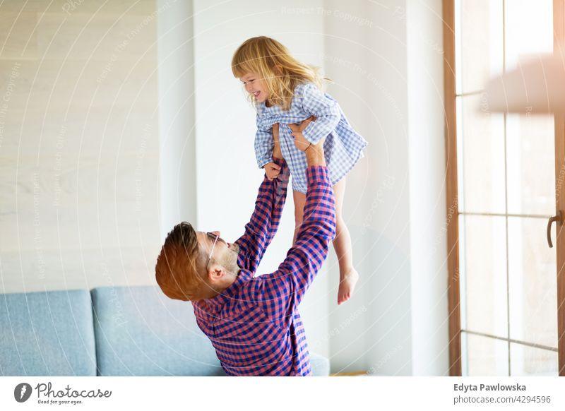 Vater spielt mit Tochter zu Hause heimwärts Mann Papa Familie Eltern Verwandte Kind Mädchen kleines Mädchen Kinder Partnerschaft Zusammensein