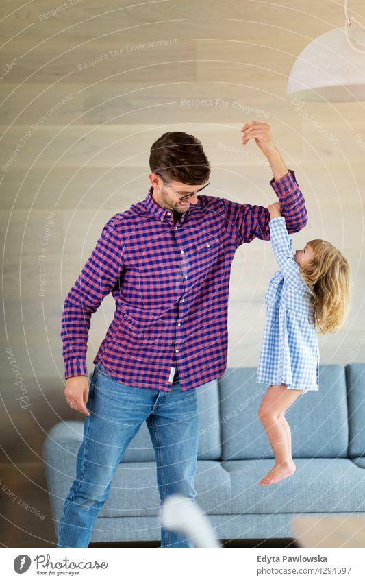 Kleines Mädchen hält sich am Arm ihres Vaters fest, als er sie hochhebt heimwärts Haus Mann Papa Familie Eltern Verwandte Kind Tochter kleines Mädchen Kinder