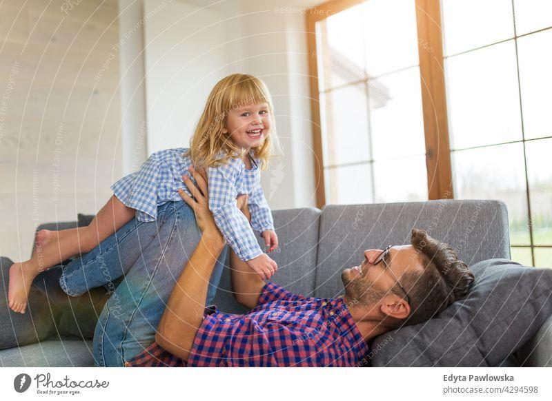 Glücklicher Vater spielt mit Tochter auf Sofa zu Hause heimwärts Mann Papa Familie Eltern Verwandte Kind Mädchen kleines Mädchen Kinder Partnerschaft