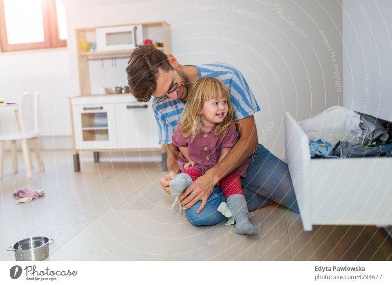Der Vater hilft der kleinen Tochter beim Anziehen heimwärts Haus Mann Papa Familie Eltern Verwandte Kind Mädchen kleines Mädchen Kinder Partnerschaft