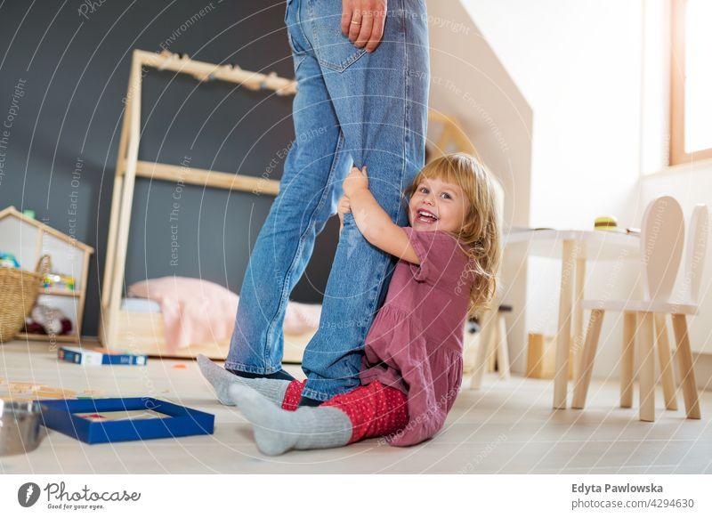 Kleines Mädchen umklammert die Beine des Vaters heimwärts Haus Mann Papa Familie Eltern Verwandte Kind Tochter kleines Mädchen Kinder Partnerschaft Zusammensein