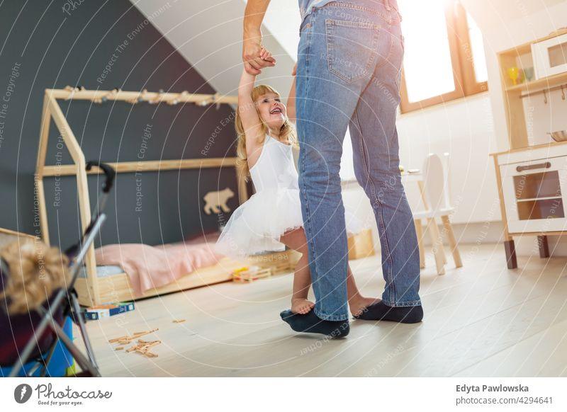 Tochter steht auf den Füßen des Vaters und tanzt heimwärts Haus Mann Papa Familie Eltern Verwandte Kind Mädchen kleines Mädchen Kinder Partnerschaft