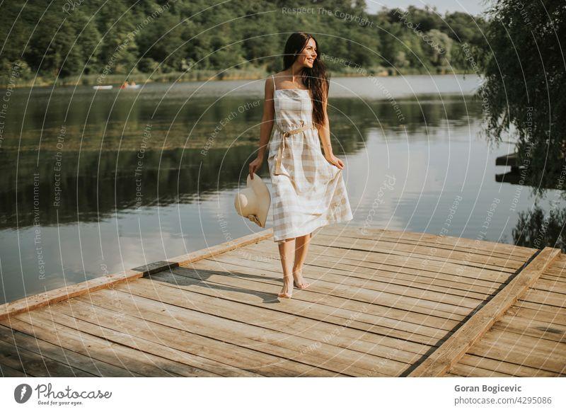 Entspannende junge Frau steht auf Holzsteg am See schön Konzept genießen Sommer Pier Natur Kaukasier gut lässig sonnig träumen Person Urlaub Freizeit ruhen