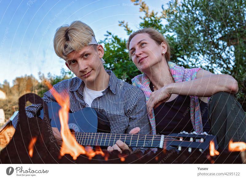 Glückliche fröhliche Mutter und Sohn sitzen im Hinterhof in der Nähe des Feuers und spielen eine akustische Gitarre. Sie singen Lieder und genießen einen Sommerabend. Sommer-Lifestyle-Fotografie. Blauer Himmel Hintergrund.