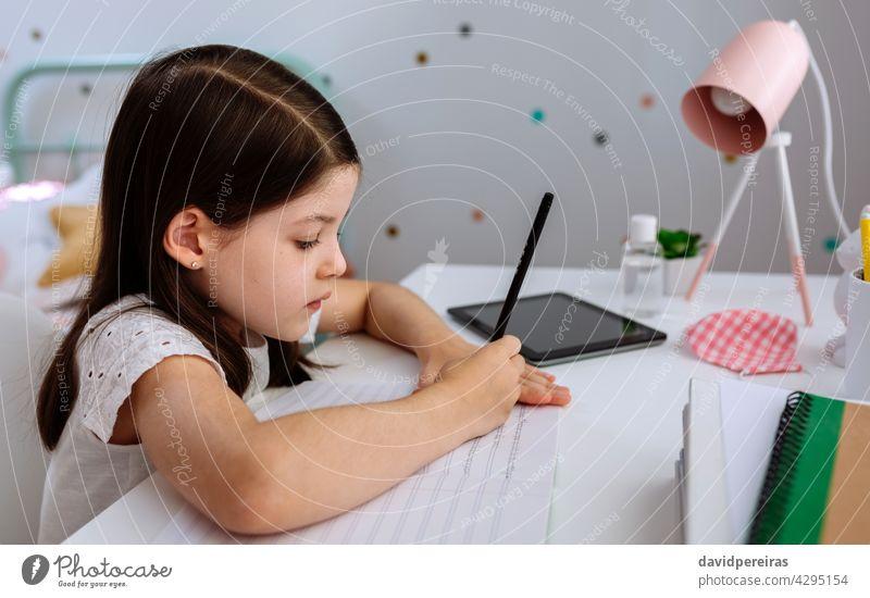 Mädchen studiert zu Hause mit Maske auf dem Tisch schreibend Schreibtisch Homeschooling Schule zu Hause Coronavirus Seuche Desinfektionsmittel heimwärts