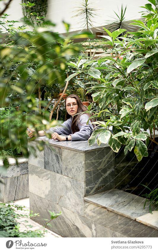 Junge Brünette Mädchen verwendet Handy Texting auf Smartphones Nachrichten macht Selfie beim Sitzen im botanischen Garten der Stadtbibliothek Frau Texten