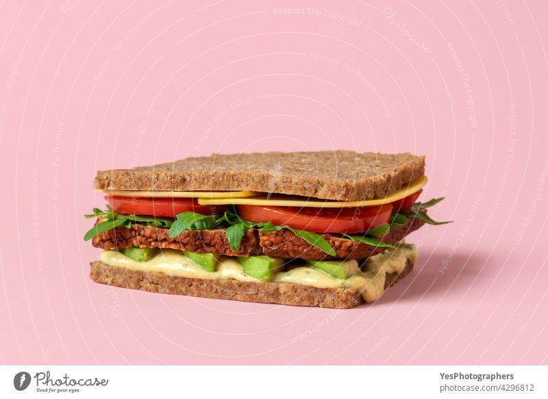 Veganes Sandwich Nahaufnahme isoliert auf einem rosa Hintergrund. alternativ Rucola Avocado Erkenntnis Brot Frühstück Burger Käse Sauberkeit Farbe