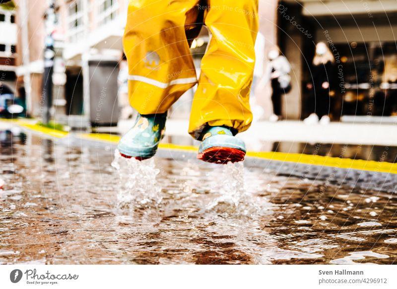 Kind springt fröhlich in eine Pfütze Wasser Spiegelung Asphalt Straße nass Reflexion & Spiegelung springen Regen Boden schlechtes Wetter Wolken Spielen fuesse