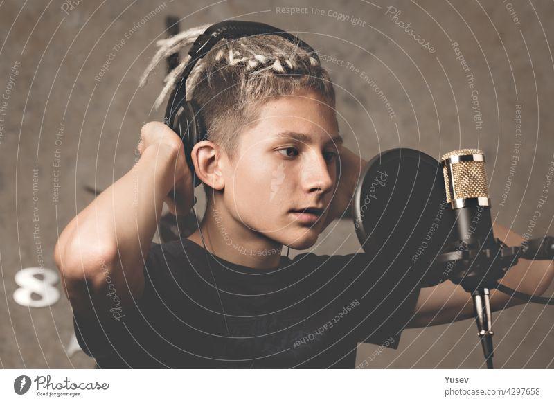Stylischer attraktiver Typ mit Dreadlocks nimmt im Studio einen Song auf. Ein junger Sänger mit schwarzen Studiokopfhörern steht vor einem Mikrofon. Generation Z junges Talent