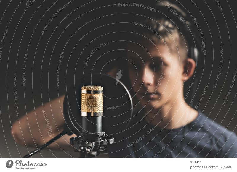Stylischer attraktiver Typ mit Dreadlocks nimmt einen Song im Studio auf. Ein junger Sänger in schwarzen Studio-Kopfhörern steht vor einem Mikrofon im unscharfen Hintergrund. Low-Key-Beleuchtung.