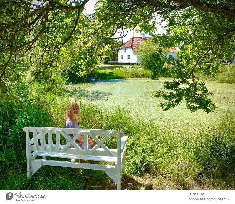Blonde Frau sitzt auf weißer Bank unter einer Eiche an einem Teich schön feminin Erwachsene Außenaufnahme Sitzbank Mensch Idylle Dänemark Sommer Lieblingsplatz