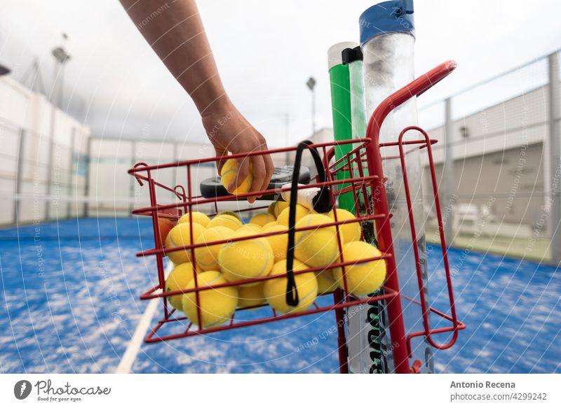 Mann fängt Bälle, um an einem bewölkten Tag mit Paddle-Tennis zu trainieren jung Training Paddeltennis Padel Gericht Sport Ball Remmidemmi Netz im Freien