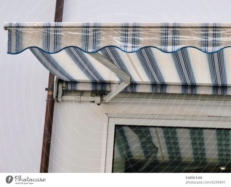 Streifen und Streifen: eine Markise spiegelt sich im Fenster. Im Raum dahinter ist es dunkel, aber es brennt noch Licht. Schaufenster Lampe Spiegelung weiß blau