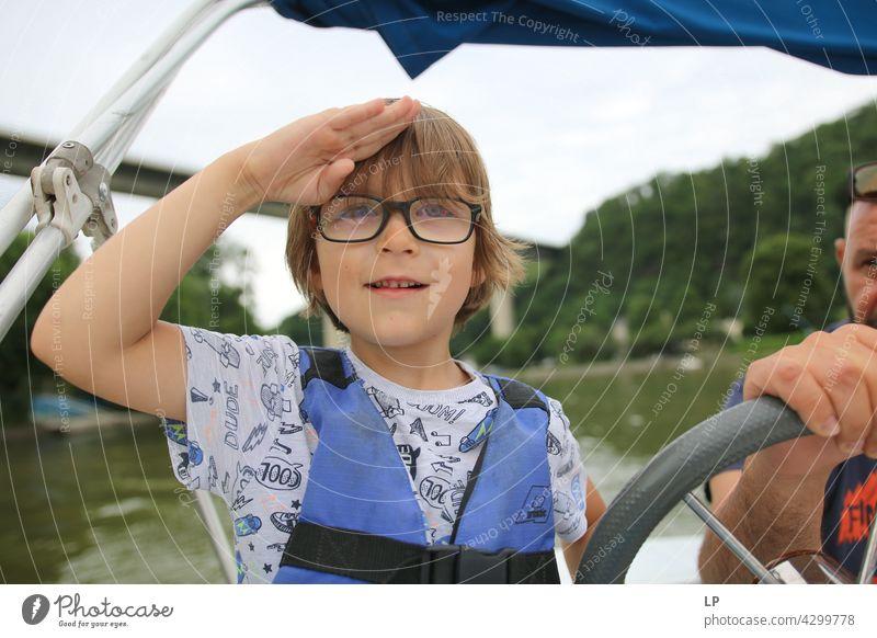 Kind mit Brille, das fröhlich zum Horizont schaut und wie ein Kapitän salutiert Mensch Gefühle Eltern Sinnesorgane Meditation Windstille Geschwister