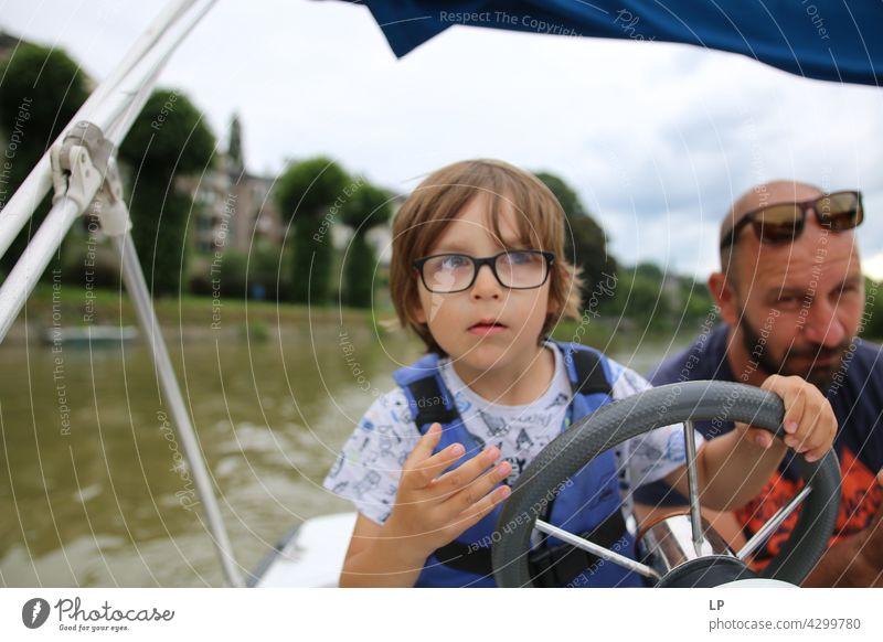 Kind mit Brille schaut zum Horizont und steuert ein Boot Mensch Gefühle Eltern Familie & Verwandtschaft Fröhlichkeit Kindheit Spielen spielerisch unschuldig