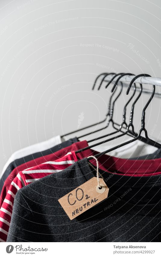 Kleidung mit Kohlenstoff-Emissionslabel Kleiderbügel Schiene kennzeichnen neutral Laden Einzelhandel Werkstatt Ablage Sekundenzeiger lässig Kauf Textil anhaben