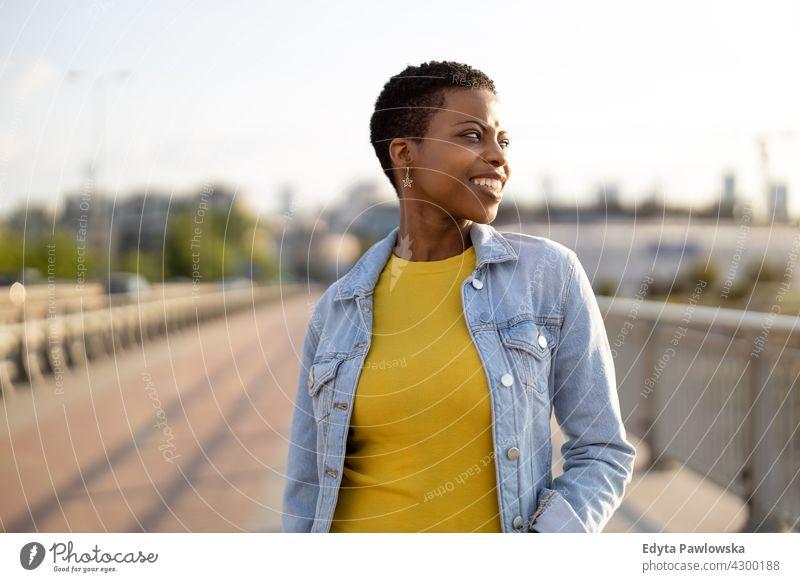 Porträt einer lächelnden jungen Frau in der Stadt Afro-Look stolz echte Menschen Stadtleben Afroamerikaner Afrikanisch Schüler schwarz Ethnizität sonnig