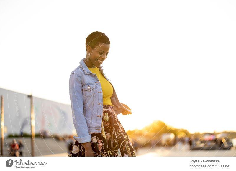 Lächelnde junge Frau genießt die Natur bei Sonnenuntergang Afro-Look stolz echte Menschen Stadtleben Afroamerikaner Afrikanisch Schüler schwarz Ethnizität