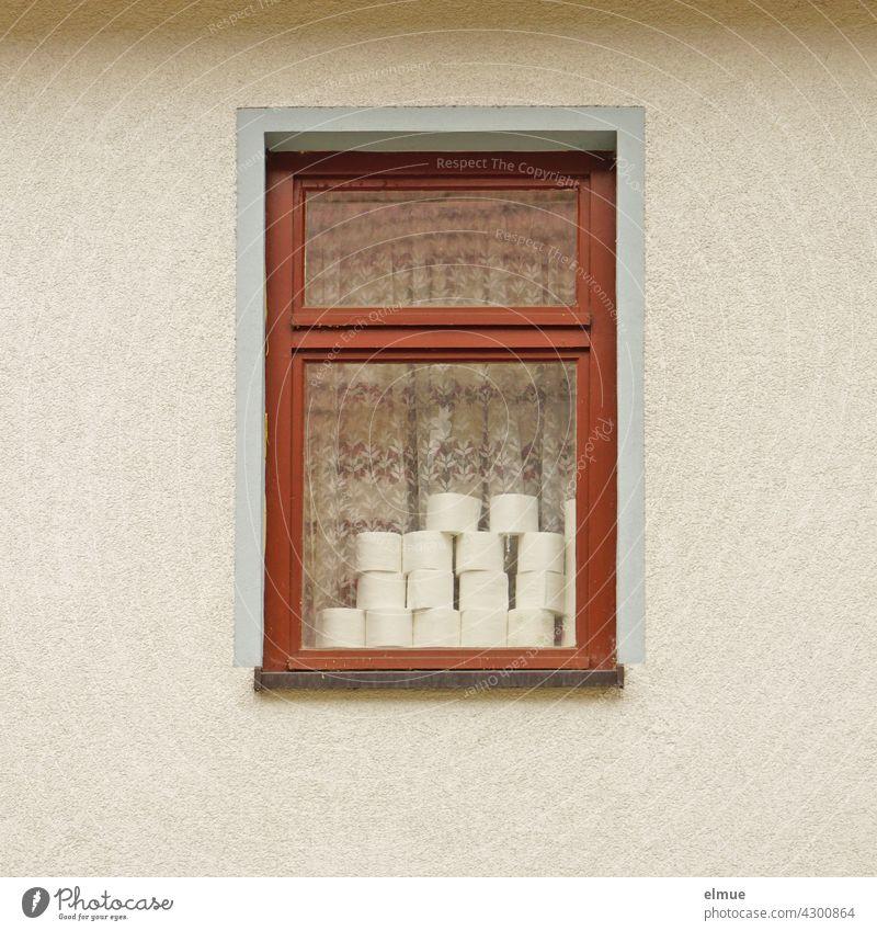Ein Spaßvogel hat hinter einem Fenster Toilettenpapierrollen gestapelt / Corona / Restbestand Klopapierrollen übrig Stapel wohnen Haus coronavirus Pandemie