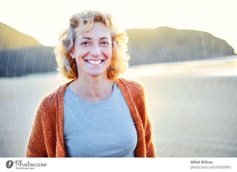 Junge reife blonde kaukasische Frau im Freien in einem Strand in einem sonnigen Tag. Lifestyle-Konzept. Porträt Wellness Frauen Gesundheit Erholung
