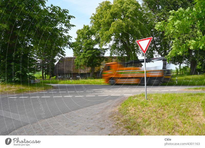 Lärm Laster Bauernhaus Landstraße Verkehr Verkehrslärm Überlandstraße Verkehrschild Vorfahrt Lastwagen Straße Verkehrswege Straßenverkehr Autofahren