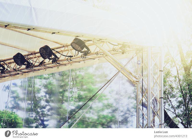 Bühnendach mit Scheinwerfern vor blauem Sommerhimmel, Sonnenschein und grünem Laub hell hoch sommerlich Licht Musik Show Konzert Open Air weiß Bäume Baumwipfel