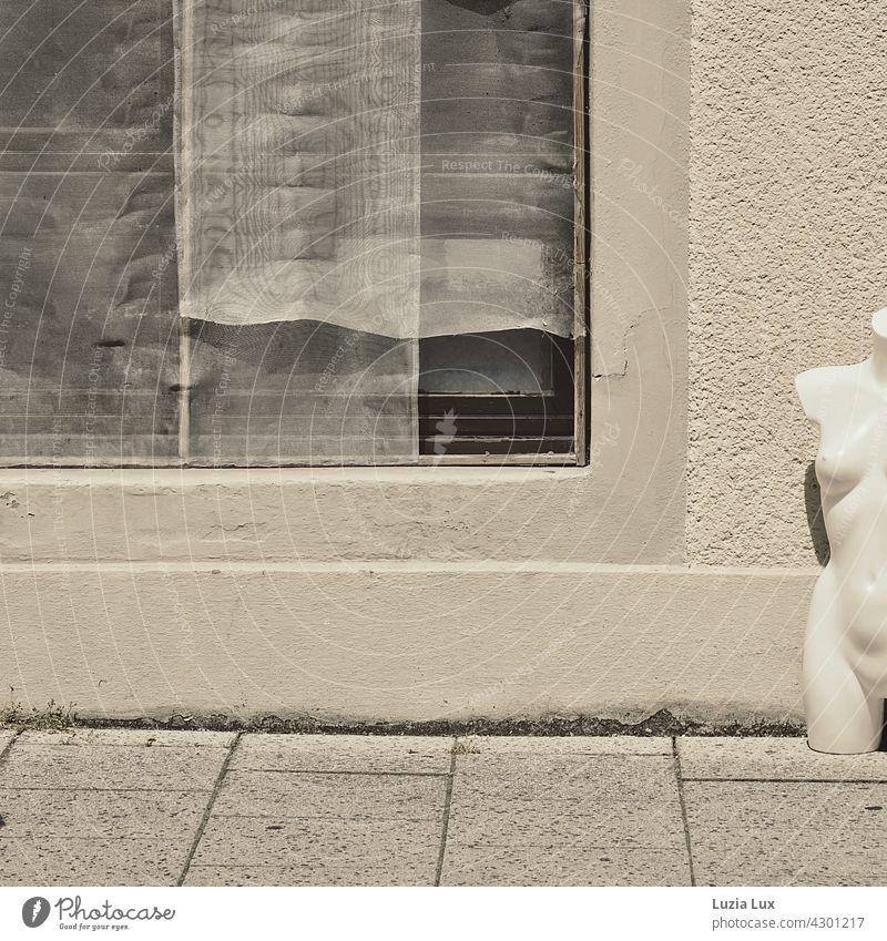 übrig und nackt... Torso einer Schaufensterpuppe steht neben einem leeren Schaufenster mit heruntergelassenen Gardinen Straße Bürgersteig Außenaufnahme Fassade