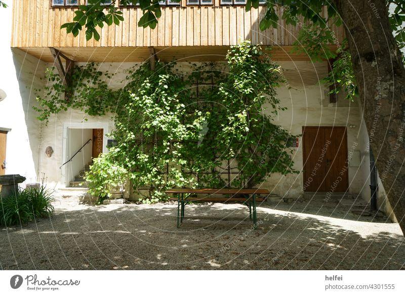 Schattiger Ruhe Platz in einem alten Landhaus mit Balkon und mit Wein bewachsene Fassade Holztisch Weintrauben rustikal Schatten kühl Feierabend Zufriedenheit