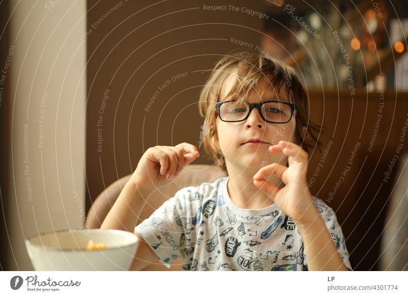 Kind mit Brille schaut neugierig in die Kamera und spielt mit seinen Fingern Stil Design Mensch Gefühle Farbfoto Eltern Kontrast Hintergrund neutral