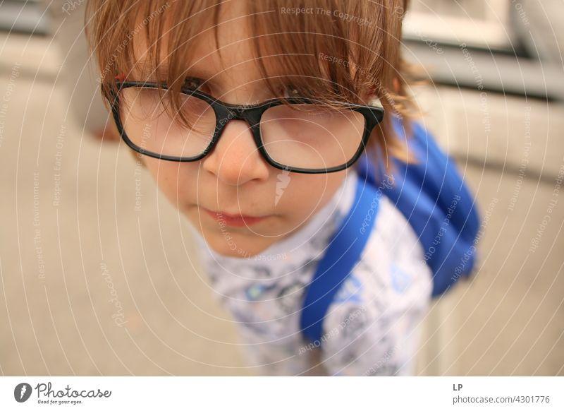 Kind mit Brille schaut neugierig in die Kamera Stil Design Mensch Gefühle Farbfoto Eltern Kontrast Hintergrund neutral Strukturen & Formen Erholung Sinnesorgane
