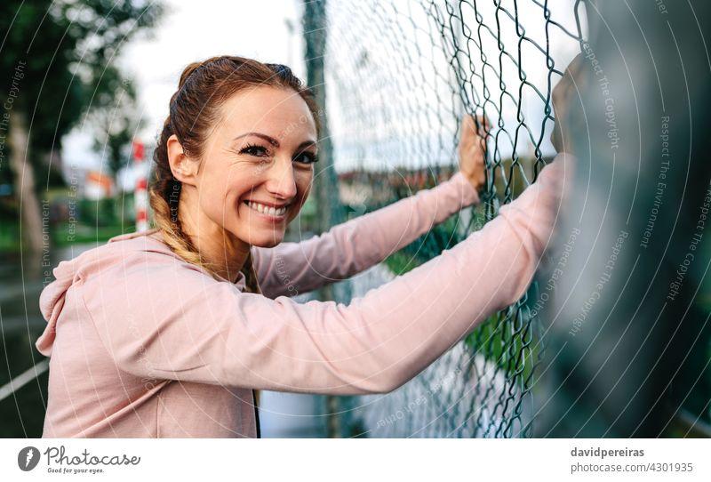 Sportlerin mit Boxerzöpfen lächelnd an einen Metallzaun gelehnt Frau Boxerflechten Lehnen Lächeln Zaun schauende Kamera aktiv freundlich Frauenpower Glück