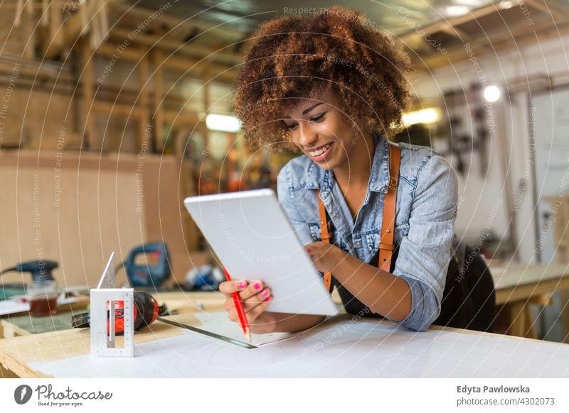 Selbstbewusste junge Frau bei der Arbeit in der Werkstatt Besitzer Beruf Dienst Kleinunternehmen Mitarbeiter arbeiten Techniker Arbeitsplatz Arbeiter