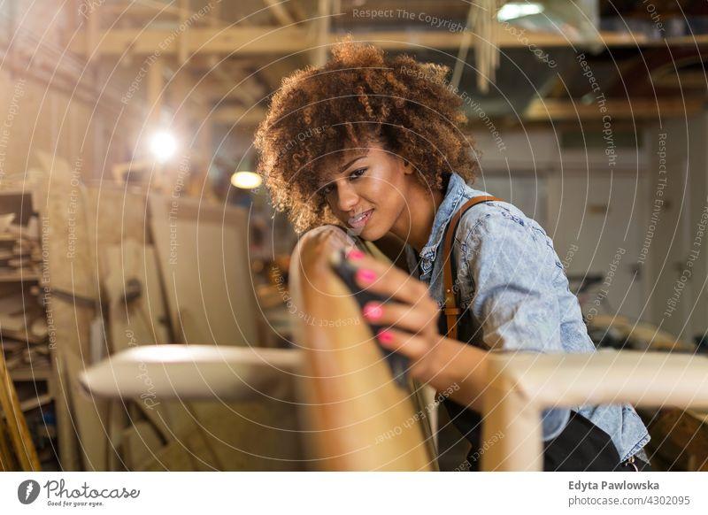 Junge Frau arbeitet an Surfbrett in ihrer Werkstatt Besitzer Beruf Dienst Kleinunternehmen Mitarbeiter arbeiten Techniker Arbeitsplatz Arbeiter Flugzeugwartung