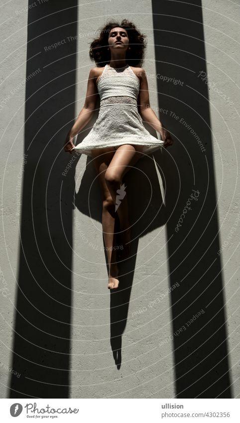 junge sexy Frau liegt zwischen zwei schwarzen Schattenstreifen auf dem Boden in der Sonne und wirft einen starken Schatten Kleid dunkel weiß geheimnisvoll