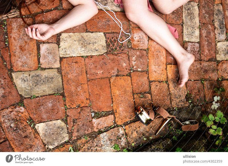 Hand, Arm und Beine einer jungen toten Frau liegen auf einem Weg aus Ziegelsteinen, Kopierraum sexy Lügen Unfall die Textfreiraum gestorben Frauen bizarr Arme