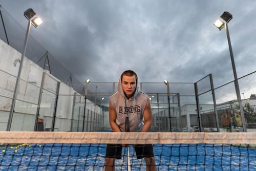 Junger Mann mit urbanen Stil Züge spielen Duell auf einem Platz im Freien jung Training Paddeltennis Padel Gericht Sport Ball Remmidemmi Netz Erholung Rasen