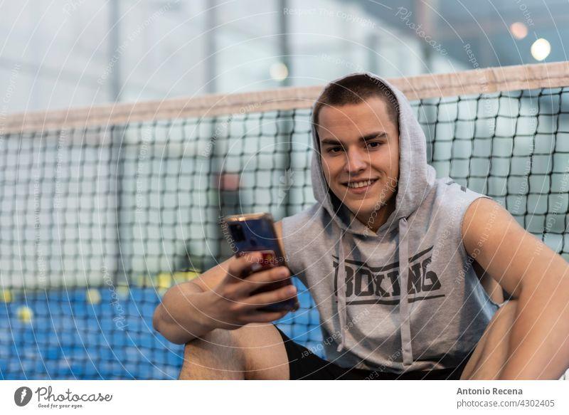 Junger Mann mit urbanen Stil nimmt eine Pause mit dem Telefon Züge nach dem Spielen Paddle-Tennis auf einem Platz im Freien jung Training Paddeltennis Padel
