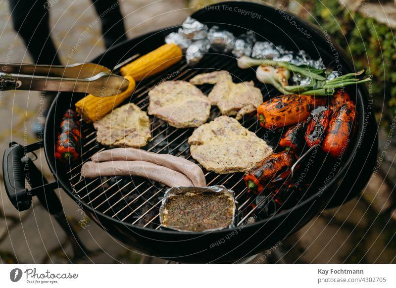 Grillen mit Fleisch und Gemüse beim Barbecue Hinterhof Grillzange Paprika Käse Essen zubereiten Kochaktion Mais Maiskolben Tag lecker Feuer Lebensmittel