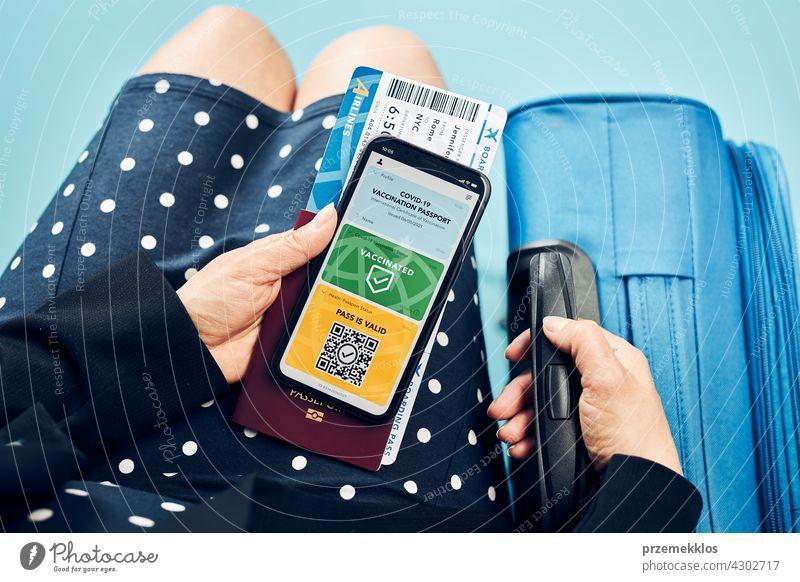 Digitaler Covid-Ausweis. Covid Impfung digitalen Pass. Frau Passagier hält digitalen medizinischen Pass auf ihrem Mobiltelefon, Reisepass und Flugticket. Reisender zeigt digitales Covid-Testergebnis als medizinischen Pass für sicheres Reisen
