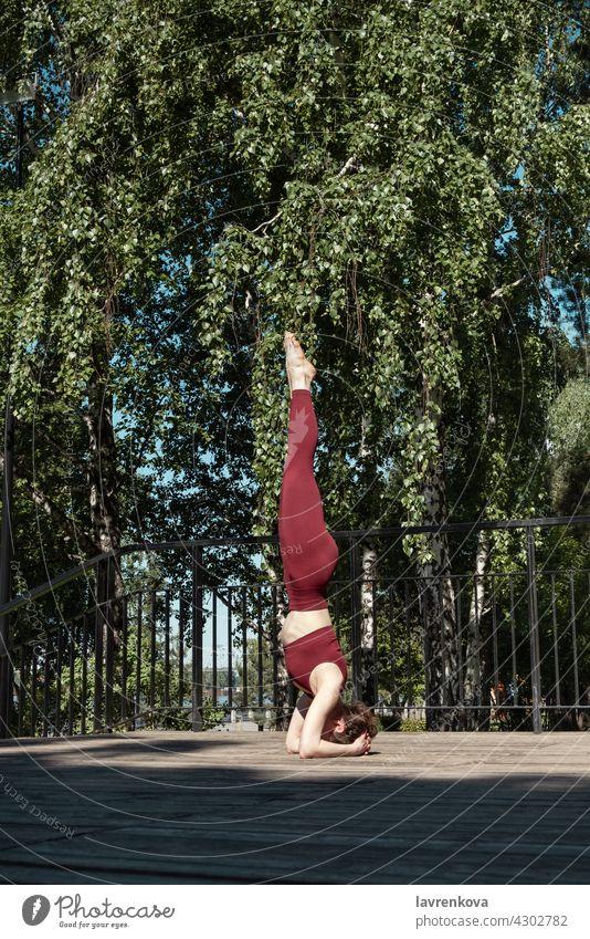 Junge brünette Frau übt Salamba Sirsasana Kopfstand Pose im Park auf Holzplattform Salamba sirsasana Kopfstand. Yoga Gleichgewicht im Freien yogini Asana Sport