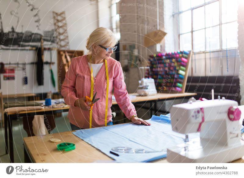Senior Modedesignerin in ihrem Atelier Nähmaschine Stoff Gewebe Material Nähen Designer Damenschneiderin Näherin Schneider Bekleidung im Innenbereich Frau