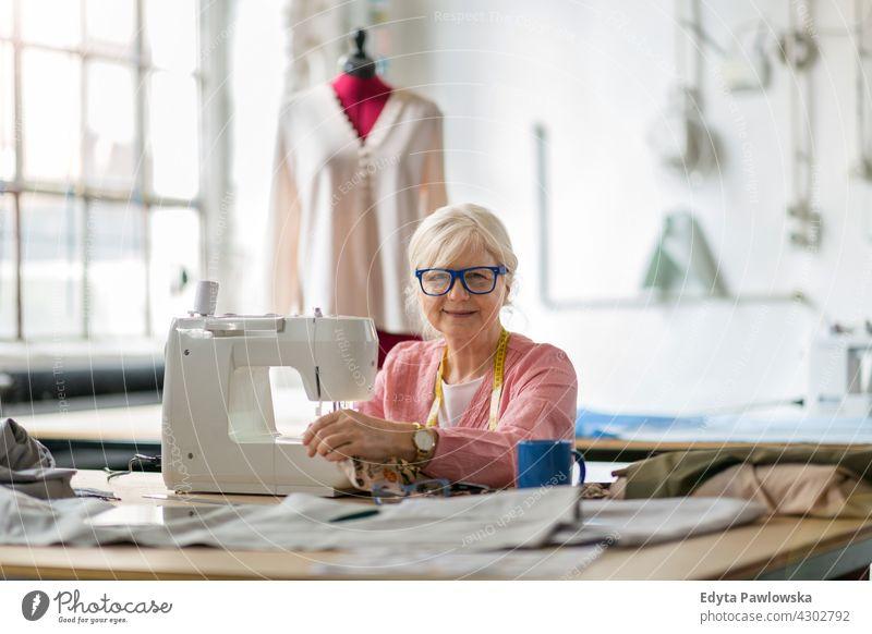 Senior-Modedesignerin an der Nähmaschine in ihrer Werkstatt Stoff Gewebe Material Nähen Designer Damenschneiderin Näherin Schneider Bekleidung im Innenbereich