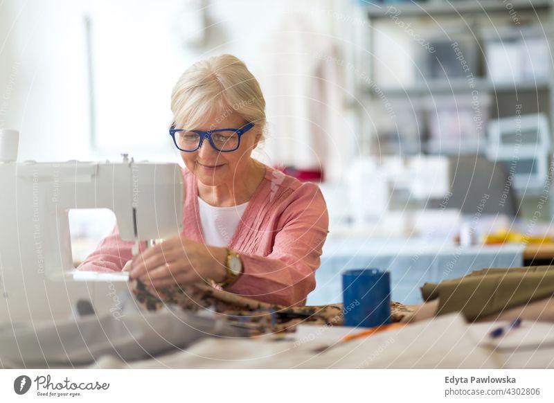 Ältere Frau an einer Nähmaschine Stoff Gewebe Material Nähen Mode Designer Damenschneiderin Näherin Schneider Bekleidung im Innenbereich Mechaniker Besitzer
