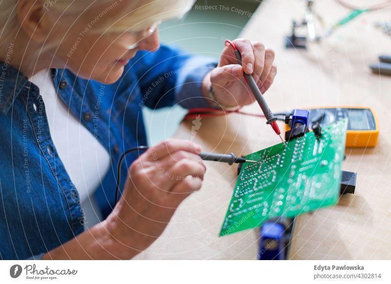 Seniorin in der Elektronikwerkstatt Messung aktuell Elektrizität Elektromonteur Ingenieur Gerät Kompetenz Industrie Job Reparatur Lötkolben löten