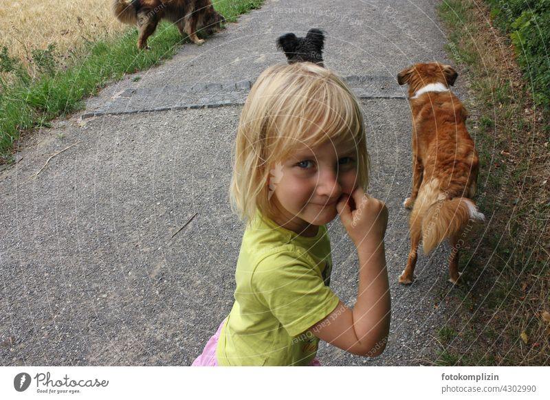 verschmitzter Blick eines Kind mit Hunden im Hintergrund fröhlich Haustier Haushund Tierliebe Weg Gassi Gassi gehen im freien Kindheit Blick in die Kamera