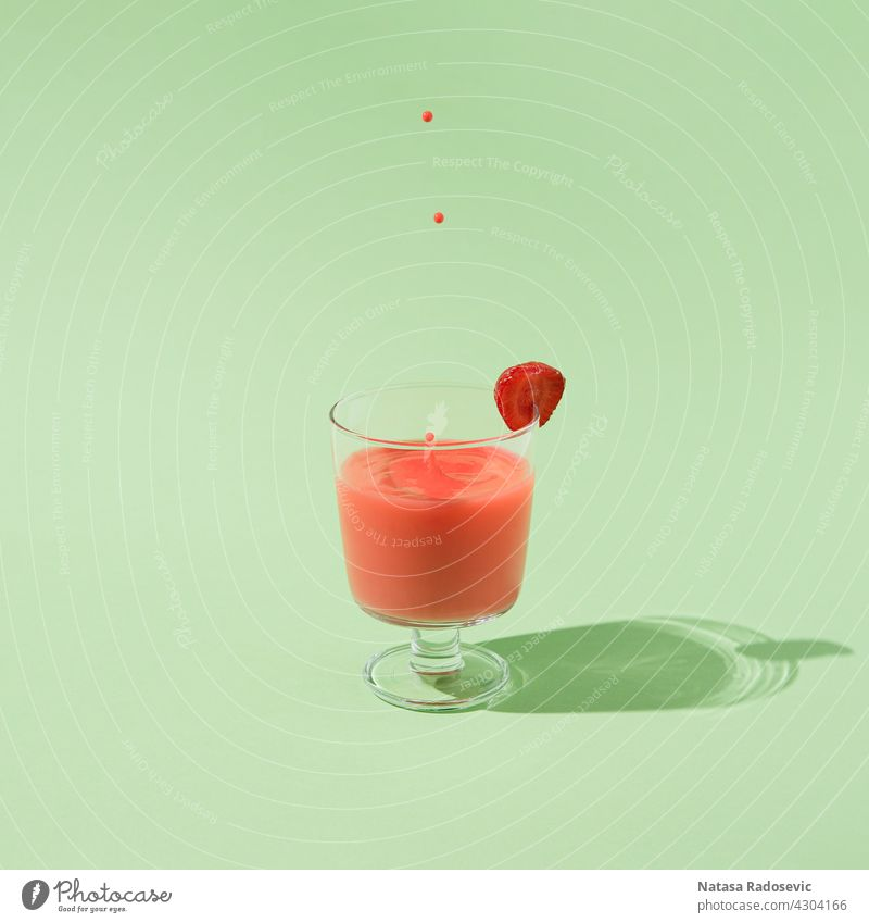 Sommer-Erdbeersaft mit fallenden Tropfen isoliert auf einem grünen Hintergrund. abstrakt sehr wenige Saft Frische Zeitgenosse Quadrat Ästhetik Kunst Getränk