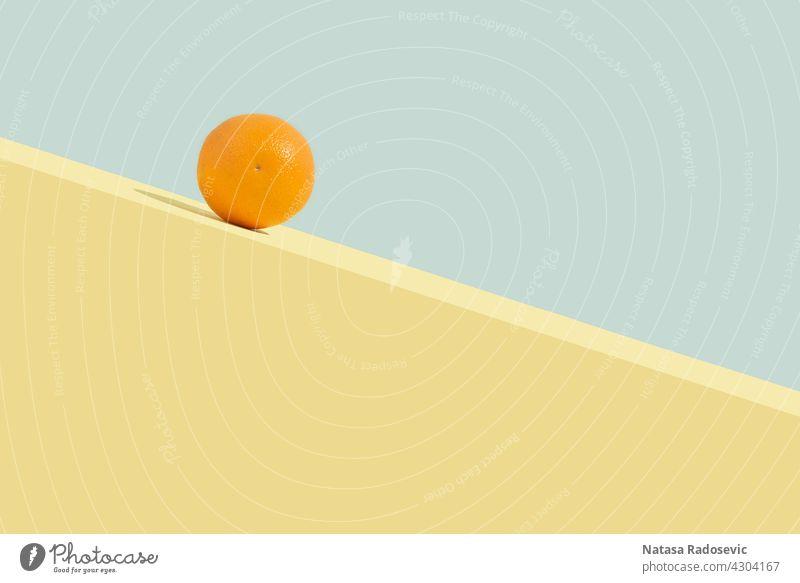 Sommerliche Orangenfrucht, die bergab rollt. Abstraktes Konzept abstrakt Zeitgenosse Rechteck Ästhetik Kunst Hintergrund blau Zitrusfrüchte Farbe farbenfroh