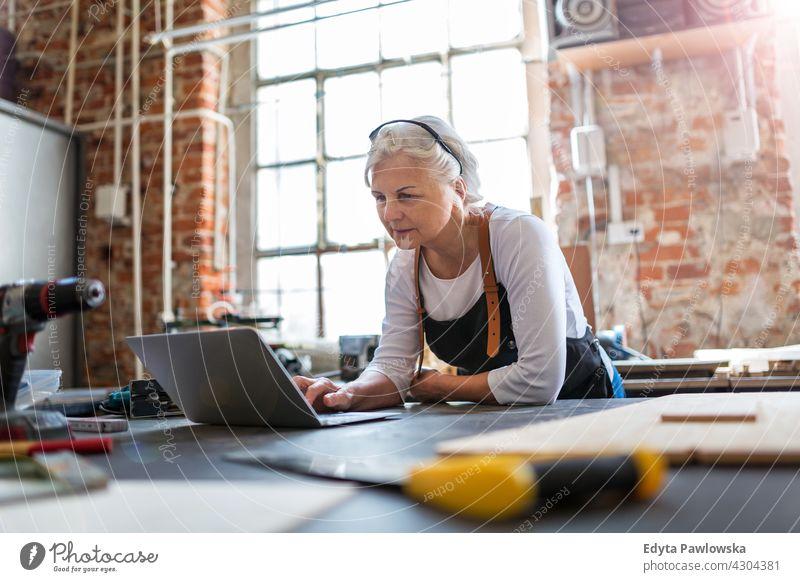 Ältere Frau mit Laptop in ihrer Werkstatt im Innenbereich Mechaniker Besitzer Beruf Dienst Kleinunternehmen Mitarbeiter arbeiten Techniker Arbeitsplatz Arbeiter