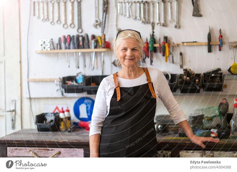 Ältere Handwerkerin in ihrer Werkstatt im Innenbereich Frau Mechaniker Besitzer Beruf Dienst Kleinunternehmen Mitarbeiter arbeiten Techniker Arbeitsplatz